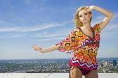 Mooi meisje in gekleurde blouseon achtergrond blauwe hemel — Stockfoto
