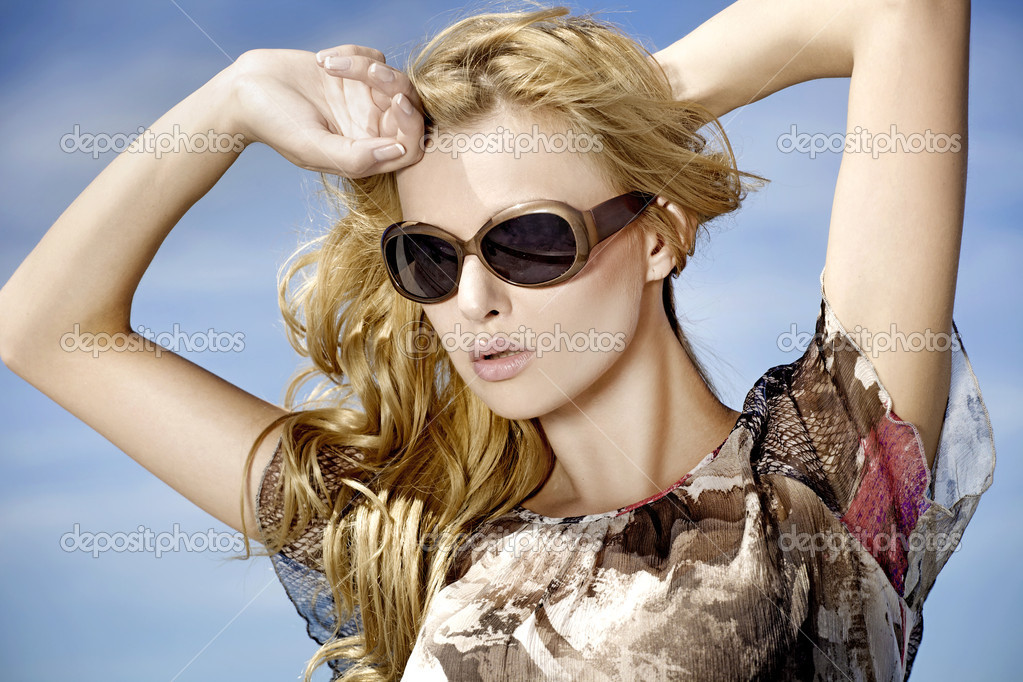 Portrait of beautiful blonde girl in sunglasses on background blue sky — Stok fotoğraf #5804221