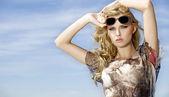 Belle fille en lunettes de soleil sur fond bleu de ciel — Photo