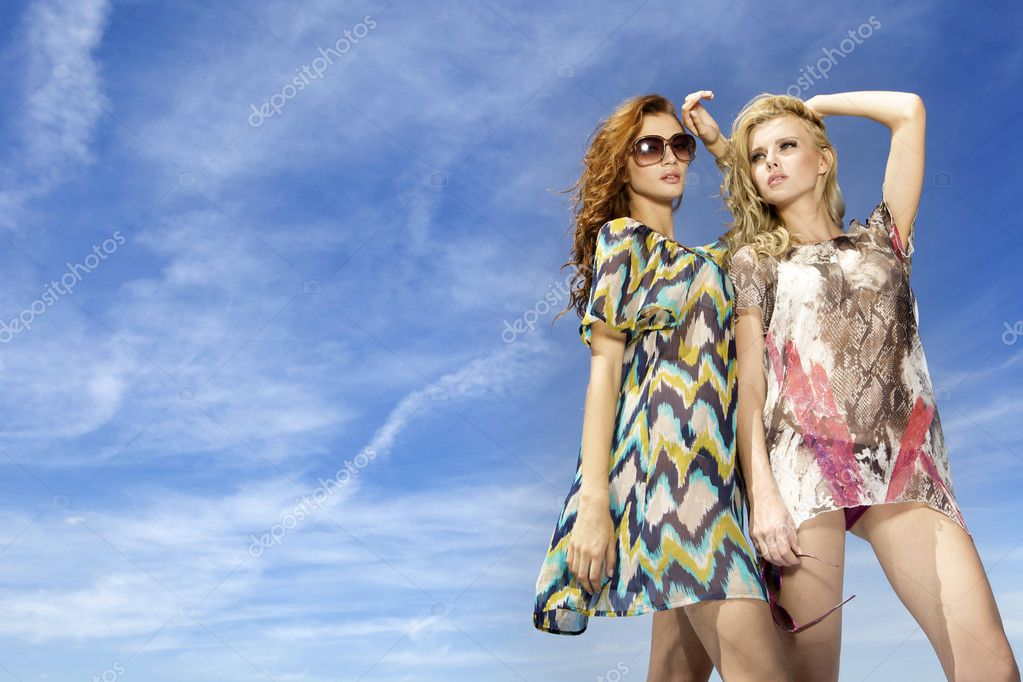 Portrait of two beautiful blonde girl in sunglasses on background blue sky — Stock Photo #5811095
