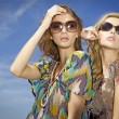 Royalty-Free Stock Photo: Two beautiful girl in sunglasses on background blue sky