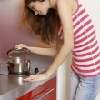 Woman standing at the kitchen - Stock Photo