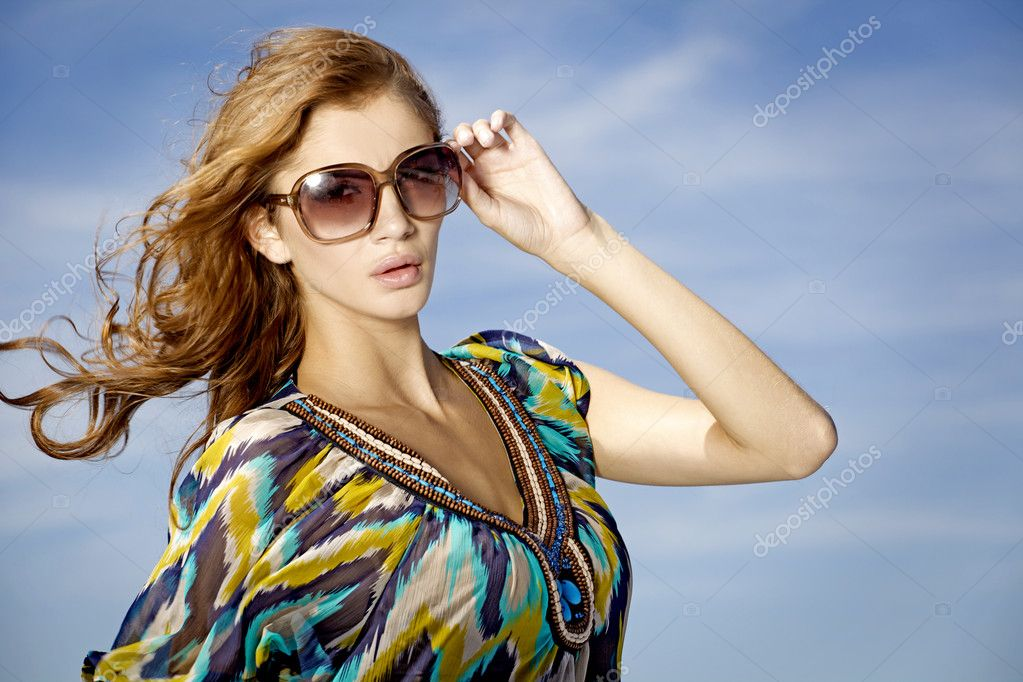 Portrait of beautiful brunette girl in sunglasses on background blue sky — Stock Photo #5833746