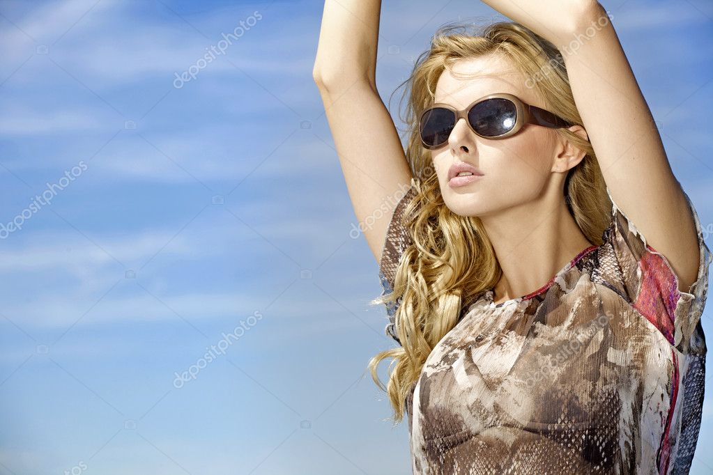 Portrait of beautiful blonde girl in sunglasses on background blue sky — Stock Photo #5833970
