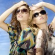 Two beautiful girl in sunglasses on background blue sky — Stock Photo #5864117