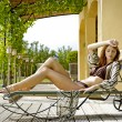 Sexy young woman relaxing on deck chair — Stock Photo #5878387