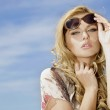 Beautiful girl in sunglasses on background blue sky — Stock Photo