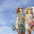 Two beautiful girl in sunglasses on background blue sky — 图库照片