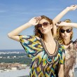 Two beautiful girl in sunglasses on background blue sky — Stock Photo #5994265