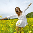 Brunette woman in a yellow flowers field — Stock Photo #5994413