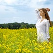Brunette woman in a yellow flowers field — Stock Photo #5994419