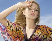 Beautiful blonde girl on background blue sky — Stock Photo
