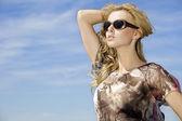 Linda garota com óculos escuros no fundo azul do céu — Foto Stock