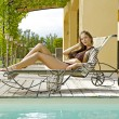 Sexy young woman relaxing on deck chair — Stock Photo #6143334