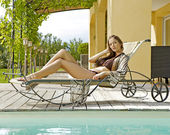Sexy young woman relaxing on deck chair — Stock Photo