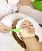 Jeune femme à obtenir un traitement de beauté peau masque sur son visage avec — Photo