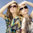 Two beautiful girl in sunglasses on background blue sky — Stock Photo #6239870