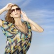 Beautiful girl in sunglasses on background blue sky — Stock Photo #6248673