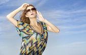Güzel bir kız üzerinde arka plan mavi gökyüzü güneş gözlüğü — Stok fotoğraf
