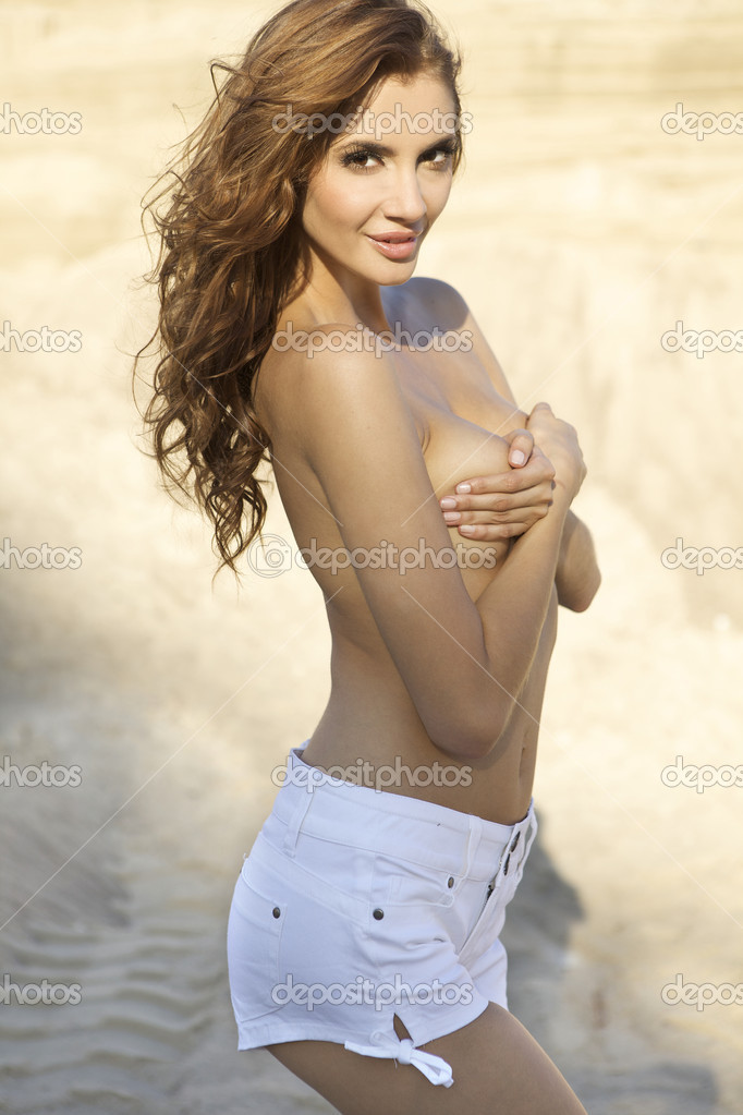 Topless sensuality brunette girl in white  jeans over sand background — Stock Photo #6262485