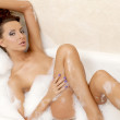 Sensual sexy girl relaxing in bath foam - Stock Photo