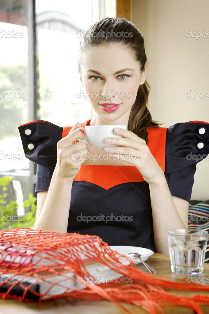 Beautiful young beunette girl with a white cup of coffee in hand, sitting in a restaurant — Stock Photo #6389042