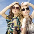 Two beautiful girl in sunglasses on background blue sky — Stock Photo