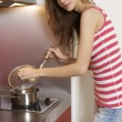 Woman standing at the kitchen - Stockfoto