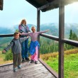 Family on wooden mountain cottage porch — ストック写真