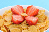Cornflakes with cut strawberry — Stock Photo