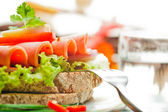 Brown bread with chili sausage slices green salad tomato and egg — Stock Photo