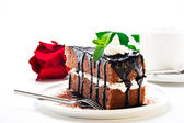 A piece of chocolate cake with vanilla cream and a rose — Stock Photo