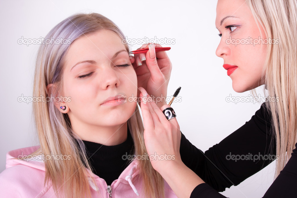 Stylist is applying eyebrow tweezers for young girl  Stock Photo #5480515