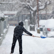 woman shoveling snow from a sidewalk after a heavy snowfall in a — Stock Photo #6148063