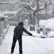 Stock Photo: Womshoveling snow from sidewalk after heavy snowfall in a