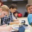 Стоковое фото: Pretty female college student sitting in a classroom full of stu