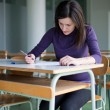 Portrait of a pretty college student working in a classroom — Stock fotografie