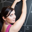 Pretty young college student drawing on the chalkboard/blackboar — Stock Photo #6148197
