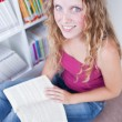 Pretty female college student in a library (shallow DOF; color t — Stock Photo
