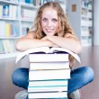 Stock Photo: Pretty female college student in a library (shallow DOF; color t