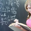 Stock Photo: Pretty young college student writing on the chalkboard/blackboar