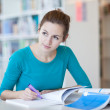 Pretty young college student in a library (shallow DOF; color to — Stock Photo #6148595