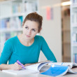 Pretty young college student in a library (shallow DOF; color to — Stock Photo #6148596