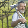Portrait of a senior man gardening in his garden (color toned im — Stock Photo