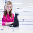 In the library - pretty, female student with laptop and books wo — Stock Photo #6148710