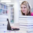 In the library - pretty, female student with laptop and books wo — Stock Photo #6148719