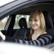 Pretty young woman driving her new car (shallow DOF; color toned — Stock Photo #6148724