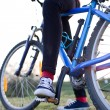 Стоковое фото: Pretty young female biker outdoors on her mountain bike (shallow