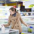 Pretty youman buying groceries in a supermarket/mall/grocery sto — Stockfoto