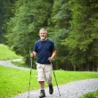 Active handsome senior man nordic walking outdoors on a forest p - Stock Photo
